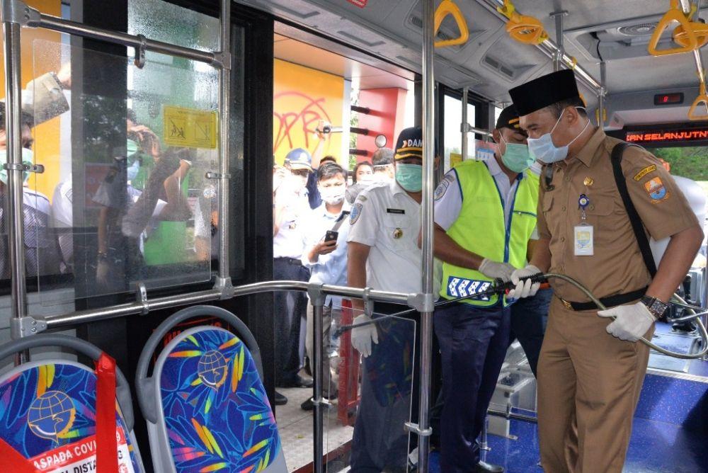 Staf ahli gubernur didampingi Kadishub melakukan penyemprotan disinfektan di bus Trans Siginjai kemarin.