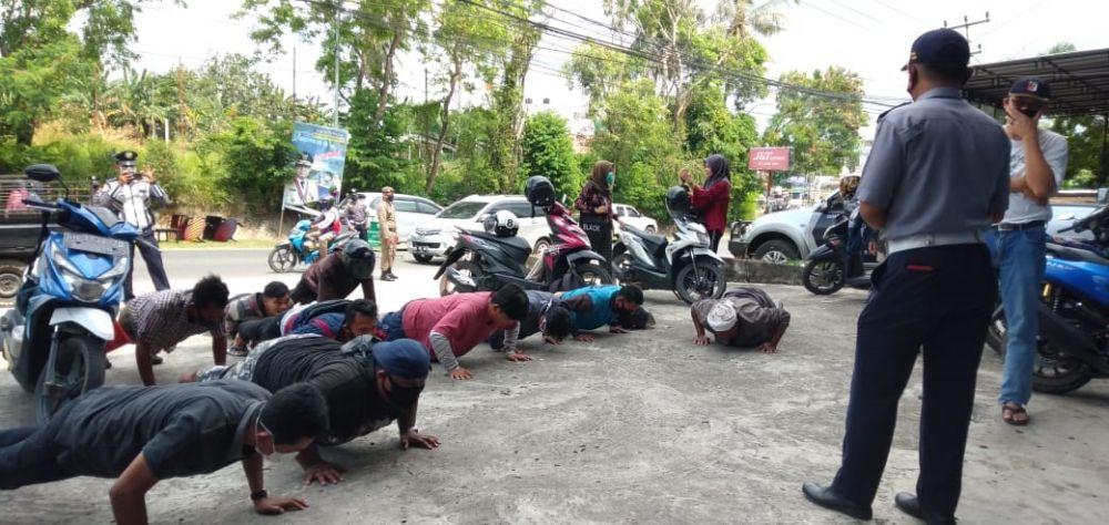 Sejumlah warga harus menjalani hukuman push up yang diberikan anggota gugus tugas Covid-19 Kota Jambi karena tertangkap tidka menggunakan masker di tempat umum.