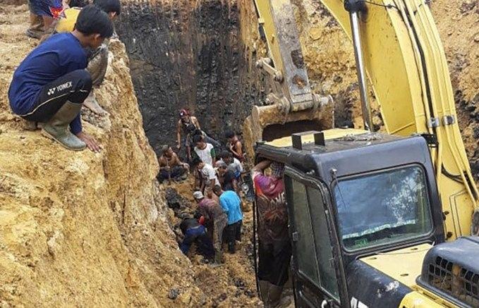 Warga dibantu alat berat berusaha mengevakuasi jenazah korban yang tertimbun longsor di Desa Tanjung Lalang Kecamatan Tanjung Agung, Kabupaten Muara Enim, Rabu (21/10). (Polsek Lawang Kidul/Antara)