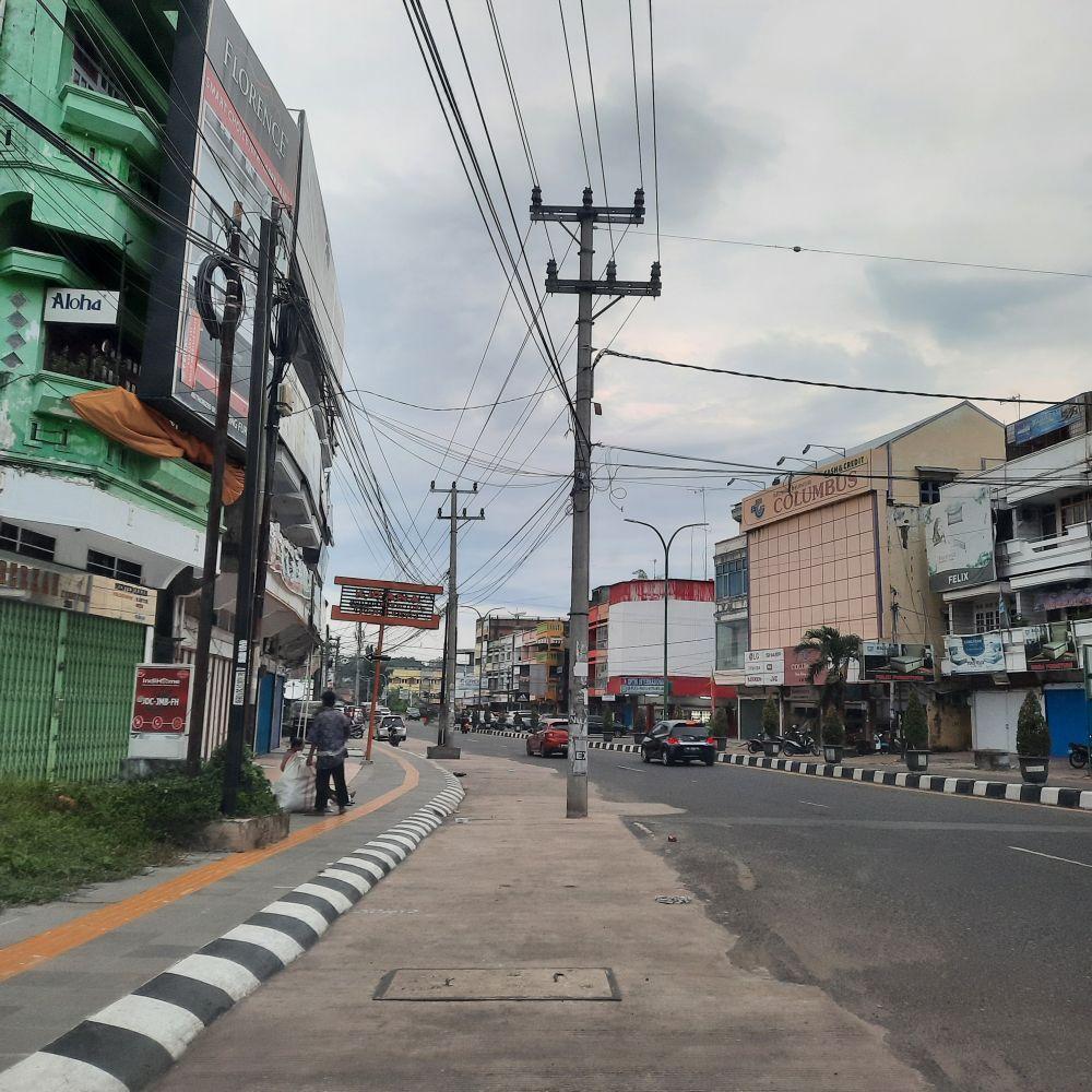 MENGGANGGU: Tiang listrik yang masih tegak di bahu jalan di Simpang Bata Kecamatan Pasar, membutuhkan relokasi agar tidak mengganggu pengguna jalan.