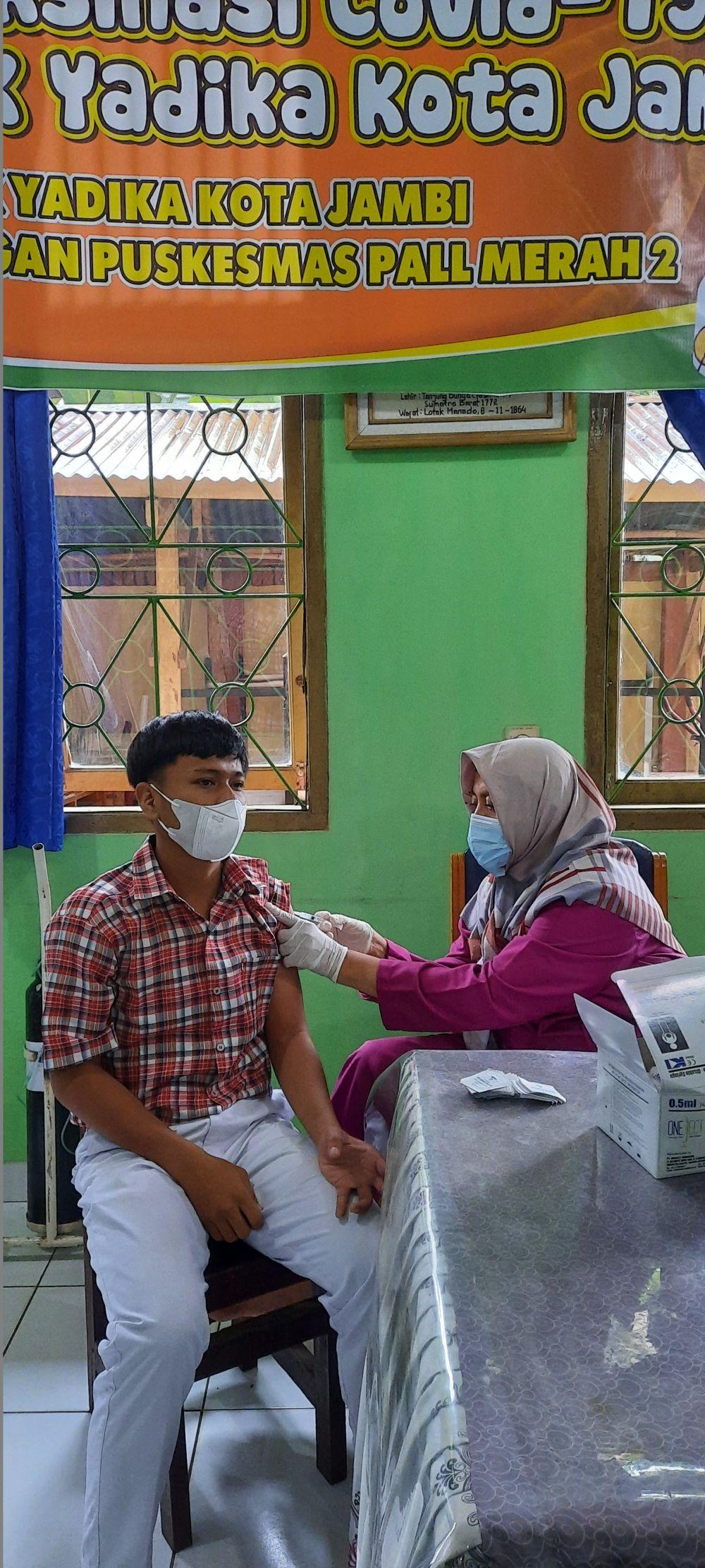 TENAGA KESEHATAN: Salah satu tenaga kesehatan tengah melakukan vaksinasi kepada siswa di Kota Jambi. Hampir Rp12 miliar insentif nakes di Kota Jambi belum dibayarkan Pemerintah Pusat.